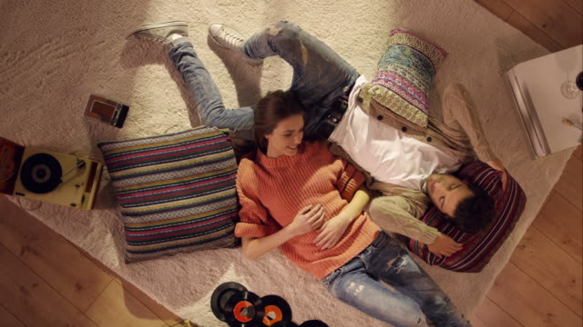 Couple lying and relaxing on carpet
