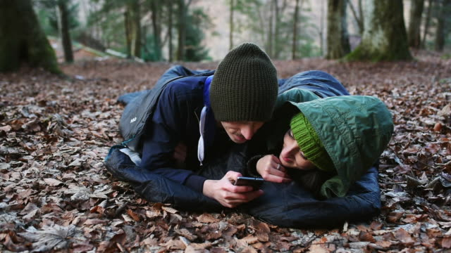 couple lying down in forest - 寝袋点の映像素材/bロール