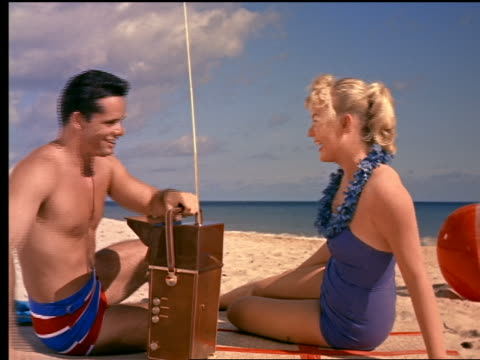 1960 couple lying down on beach + watching portable television - 1960 stock-videos und b-roll-filmmaterial