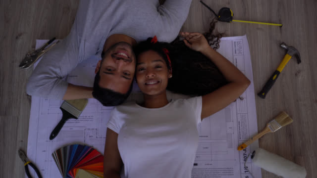 couple lying down on top of a blueprint with tools around facing camera smiling after doing a home renovation - colour sample stock videos & royalty-free footage