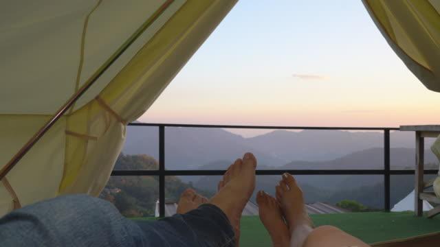 paar liegt im zelt mit bergblick - idyllic stock-videos und b-roll-filmmaterial