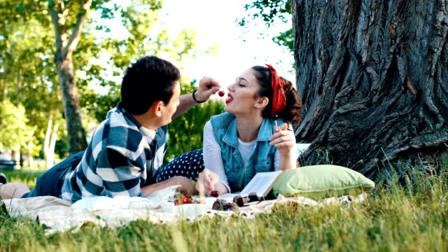 vídeos de stock e filmes b-roll de couple lying on a blanket and feed each other with a cherry - picnic