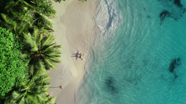 a couple lying on a tropical beach - clima tropicale video stock e b–roll