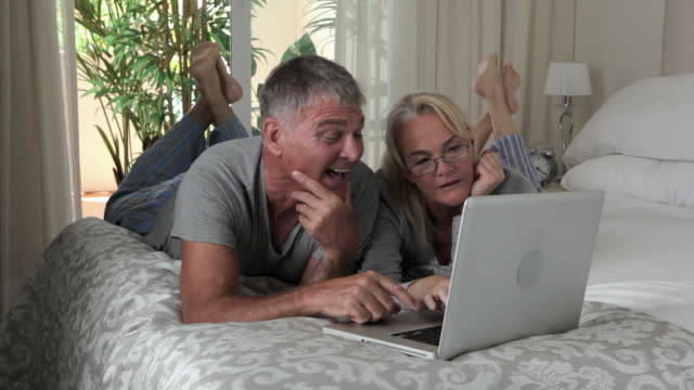 Couple lying on bed with laptop