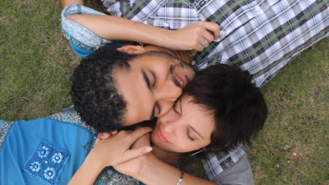 cu couple lying on grass, rubbing cheek / havana, cuba - auf dem rücken liegen stock-videos und b-roll-filmmaterial