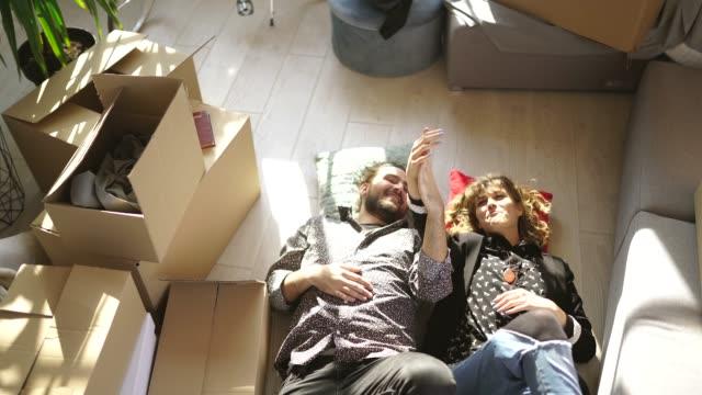 vídeos y material grabado en eventos de stock de pareja tumbado en el piso en apartamento nuevo - hípster urbano
