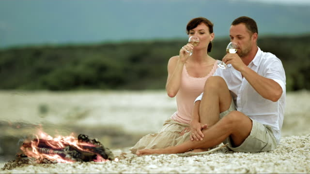 slo mo couple making a toast on beach by fire - mid adult men stock videos & royalty-free footage