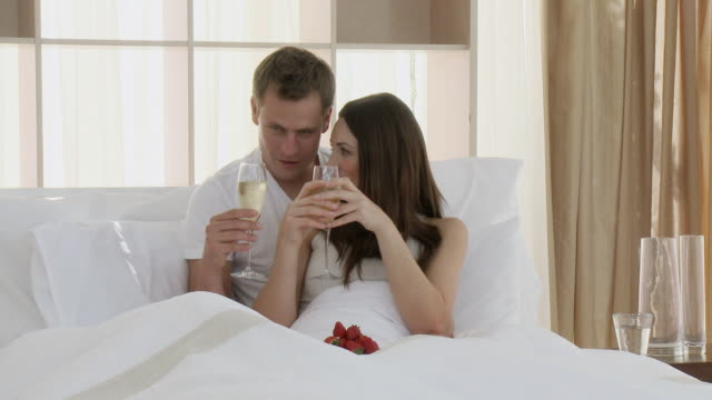 MS Couple making a toast with champagne in bed / Cape Town, Western Cape, South Africa