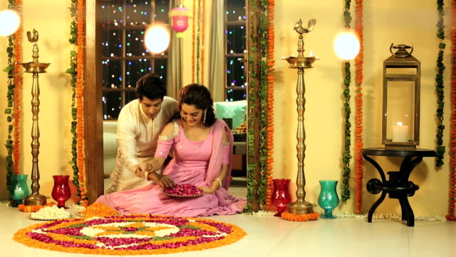 MS PAN Couple making flower rangoli for Diwali celebrations