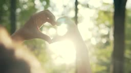 Couple making heart shape with hands at sunset on at sunset at park