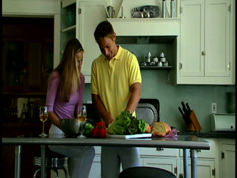 couple making salad - dreiviertelansicht stock-videos und b-roll-filmmaterial
