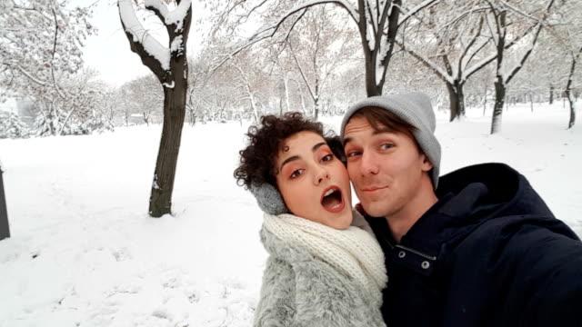 vídeos de stock, filmes e b-roll de casal fazendo selfies na neve - protetor de ouvido