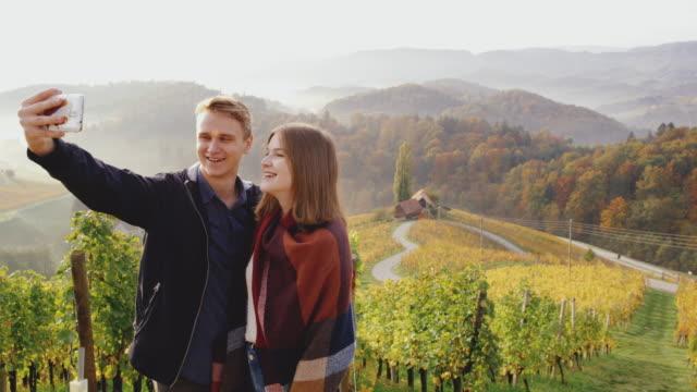 vidéos et rushes de couple ds faire selfies avec coeur en forme de route de campagne en arrière-plan - touriste