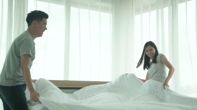 couple making the bed together - sheet bedding stock videos & royalty-free footage