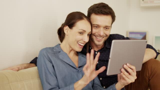 vídeos y material grabado en eventos de stock de pareja para hacer video llamada a través de tablet pc en el hogar - 40 44 años
