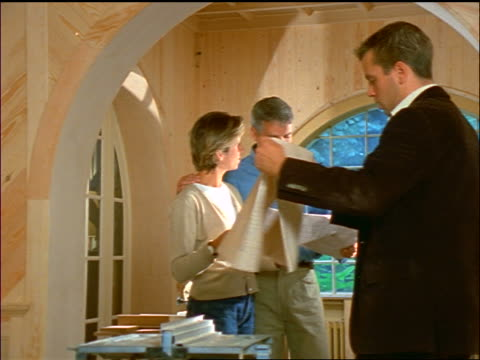 couple + male architect looking over blueprints in unfinished house - einzelne frau mit männergruppe stock-videos und b-roll-filmmaterial