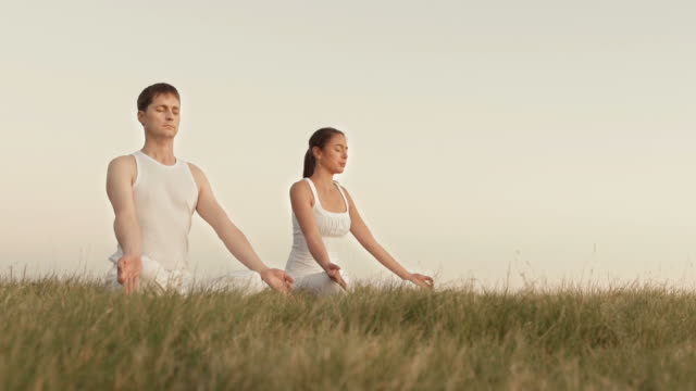 hd: couple meditating in the nature - alternative lifestyle stock videos & royalty-free footage