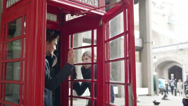 DS paar ontmoeten op de rode telefooncel