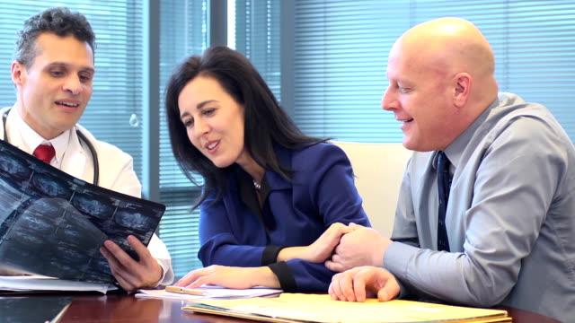 vídeos de stock, filmes e b-roll de casal se reunir com a equipe médica a falar de tratamento - cirurgião