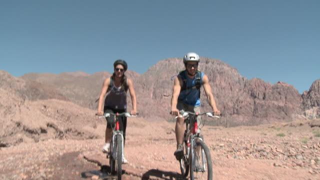 Couple mountain biking in rocky landscape