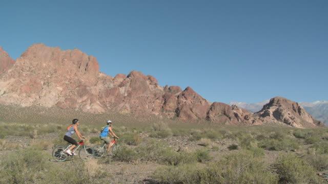 stockvideo's en b-roll-footage met couple mountain biking through rocky landscape - argentijnse etniciteit