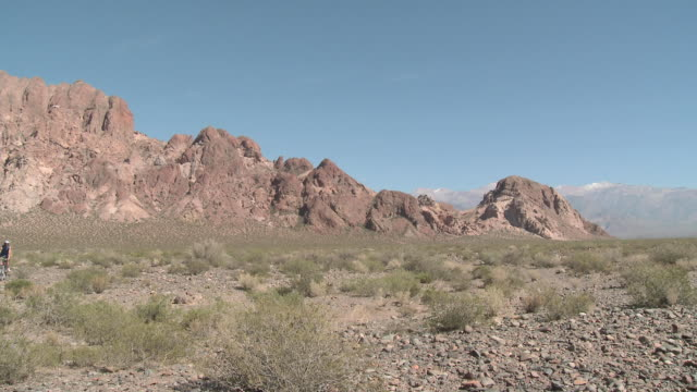 Couple mountain biking towards camera in rocky terrain