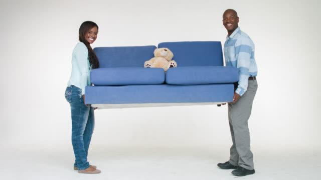 Couple moving a sofa
