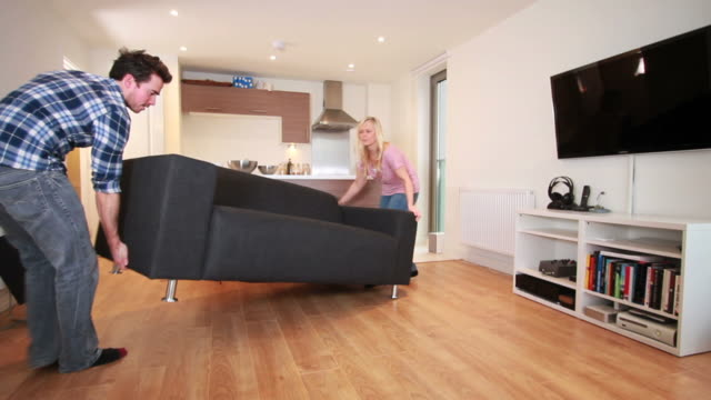 couple moving sofa in new home - furniture stock videos & royalty-free footage