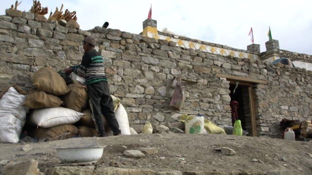 couple moving stuff in front of their stone house in the village of karzok in ladakh, india - stone house stock videos & royalty-free footage