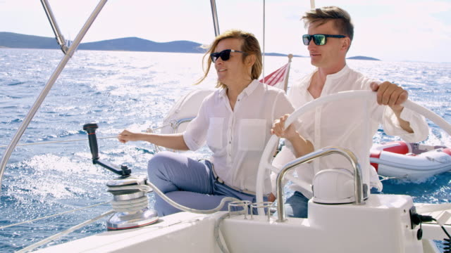 ws couple navigating a sailboat on the sea - team captain stock videos & royalty-free footage