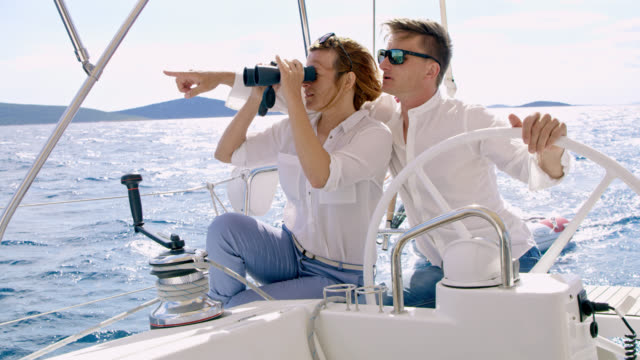 ws couple navigating a sailboat to its destination - binoculars stock videos & royalty-free footage