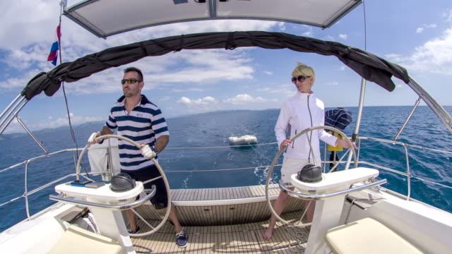 WS Couple Navigating A Sailboat