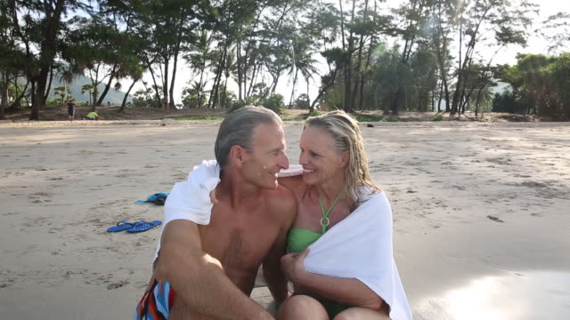 couple nestle under towel near beach edge, surf - towel stock videos & royalty-free footage