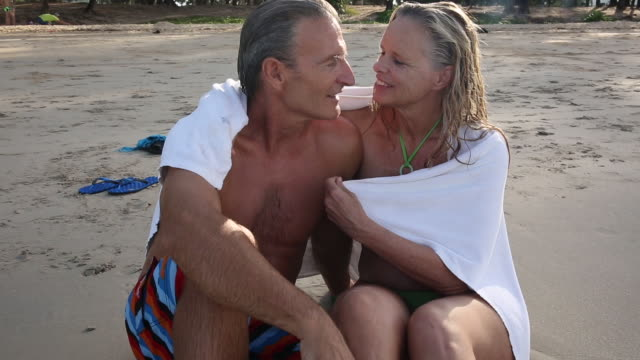 カップルは、ビーチの端、サーフィンに近いタオルの下でネスレします。 - タオルにくるまる点の映像素材/bロール