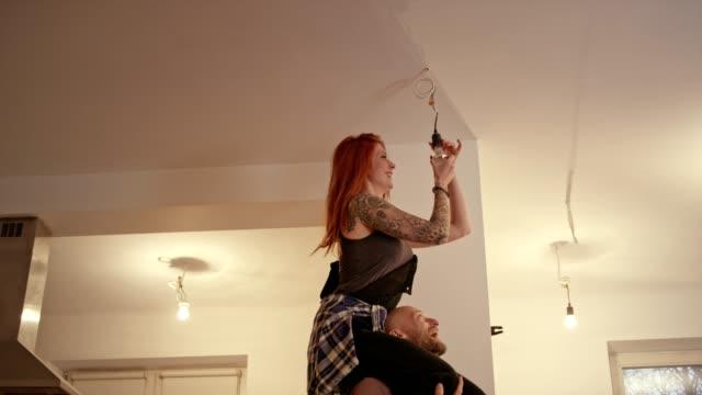 vídeos de stock e filmes b-roll de couple new home changing light bulb piggyback fun - arranjo