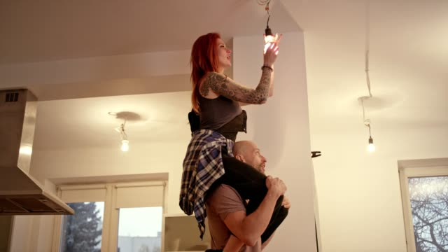 couple new home changing light bulb piggyback fun - changing lightbulb stock videos & royalty-free footage