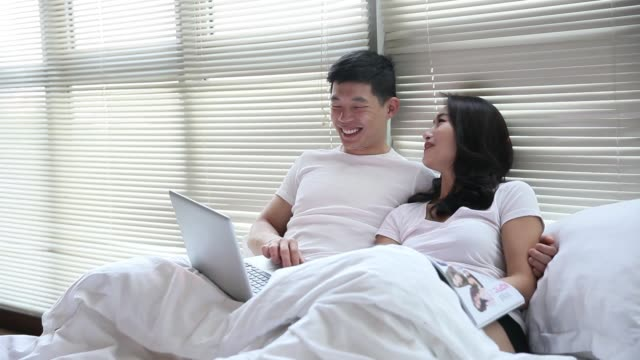 couple ob bed browing internet using laptop and talking to each other - tan stock videos and b-roll footage