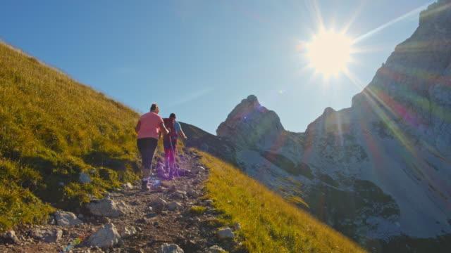 stockvideo's en b-roll-footage met ws paar van een bergwandelaar wandelen op een pad - julian alps