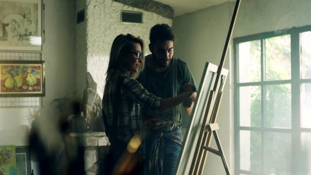 vidéos et rushes de couple d'artistes travaillant ensemble - toile à peindre