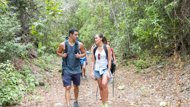 Couple of backpackers hiking with friends