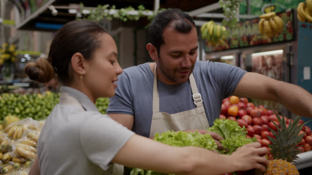 couple of employees organizing retail display with fruits and vegetables - market trader stock videos & royalty-free footage