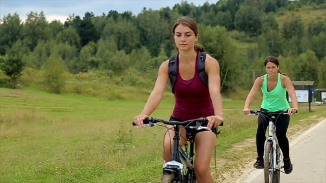 couple of female friends riding bikes on the street. - mountain bike stock videos & royalty-free footage