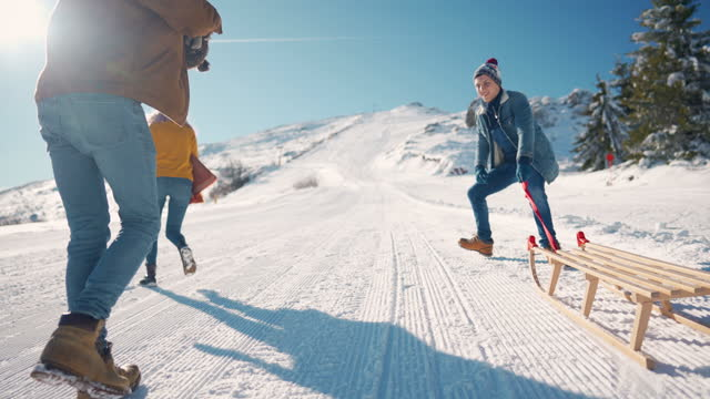 couple of friends moving uphill and pulling a sled together ready to have fun - sledge stock videos & royalty-free footage