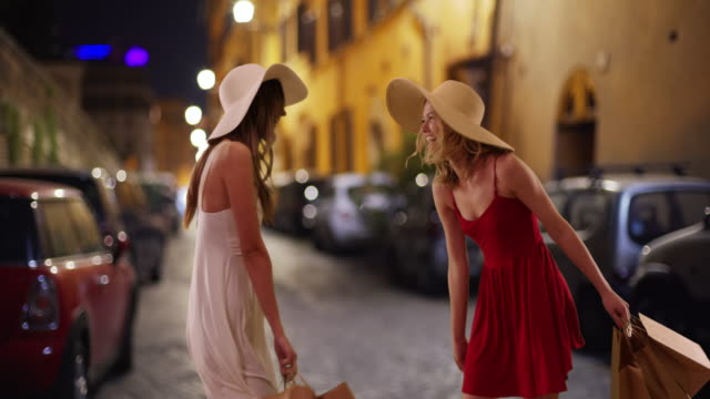 couple of fun white girls twirling in summer dresses after shopping in rome - persona attraente video stock e b–roll