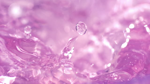 vídeos de stock e filmes b-roll de a couple of ice cubes falling into swirling light pink hued water and making waves, splashes and bubbles, in close up and slow motion. - cor de rosa