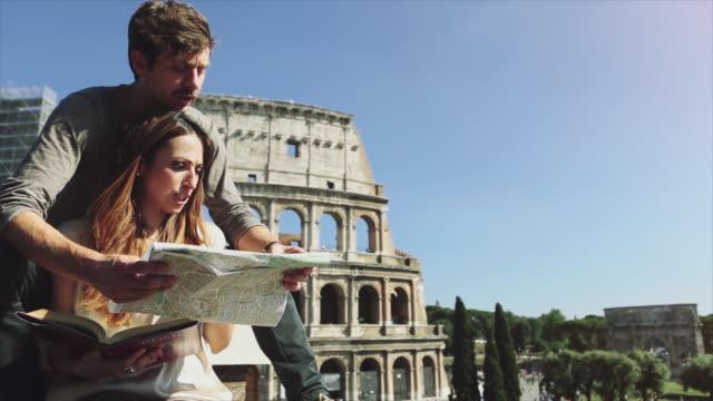 stockvideo's en b-roll-footage met paar minnaar toeristen in rome door het colosseum - colosseum