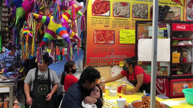 couple of lovers kiss at the counter of a restaurant in the coyoacan market, colorful pinatas in the background on december 12, 2020 in mexico city,... - papier stock videos & royalty-free footage