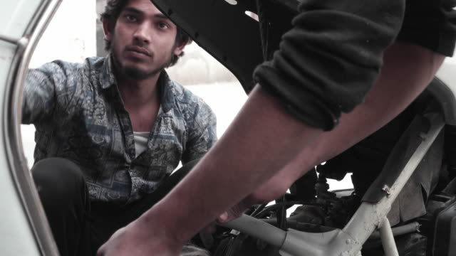 A couple of mechanics working on a two wheeler at a road side repair shop