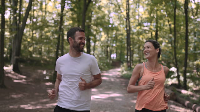 couple of mid adult athletes running together. - mid adult couple stock videos & royalty-free footage
