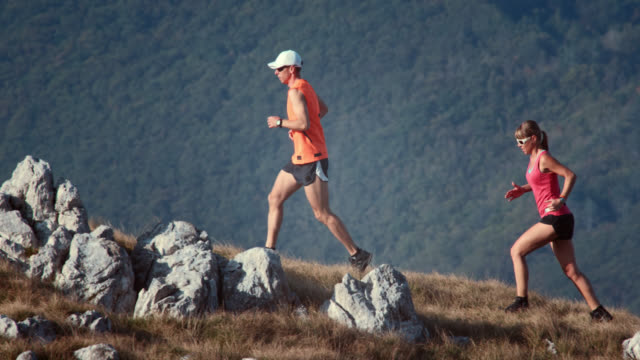 stockvideo's en b-roll-footage met couple of mountain runners running up the hill - baseballpet
